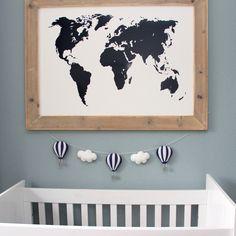 Een stoere babykamer. Steigerhouten lijst met een witte plaat, daarop zit een donkerblauwe wereldkaart muursticker. Luchtballonnen slinger is van Kidsware