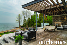 An outdoor lounge area with lake views! And a hot tub, with gorgeous outdoor furniture sectional couch.