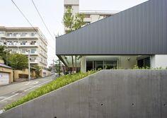 敷地面積211m2、建築面積84m2、延床面積157m2。二方向に傾斜した敷地で元は擁壁で囲まれていた。周囲への圧迫を抑えるため片面を斜めにし、建物も1階を半地下状に埋め、建物の高さも抑えている。 japan-architects.com