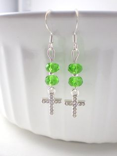 These bright green earrings are composed of light green beads, silver spacer beads, and glittery cross crystal charms. These light green cross earrings add the perfect touch of green for any day. These earrings come in a cute organza bag ready for gifting.  LENGTH: 1 & 3/4 inches (ear wire to end of lowest bead)