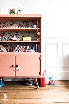 A child's bookshelf with toys and books