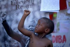 Les enfants derrière MandelaAFRIQUE DU SUD, Pretoria. Un enfant lève le poing en soutien à l'ancien président d'Afrique du Sud Nelson Mandela, hospitalisé après une infection pulmonaire, le 14 juillet 2013. REUTERS/Christopher Furlong