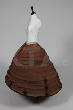 A brown cotton crinoline, circa 1860, of brown wool, with velvet coverd buttons, velvet cutwork adornnments, tape covered metal struts This crinoline dates about 1863 and is current in the HiLiCoN collection in the Netherlands. The condition is poor, but is a rare big and colored model.