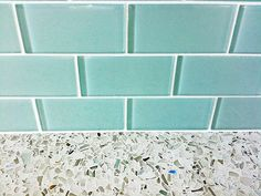 Turquoise glass subway tile backsplash with recycled glass countertops in kitchen