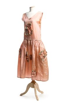 Pink silk robe de style dress, 1920s. This lovely dress is ornamented with pink and green silk rosettes. The full, gathered skirt has sewn in hip panniers, an innovation introduced by designer Jeanne Lanvin in 1915 to feminize the straight silhouette popular at this time and the later boyish, flapper style of the 1920s