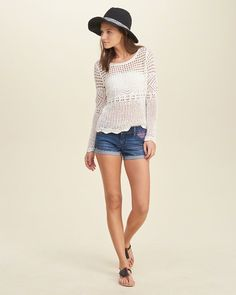 A breezy sweater with open stitching, pretty crochet, a rolled neck and scalloped hem.