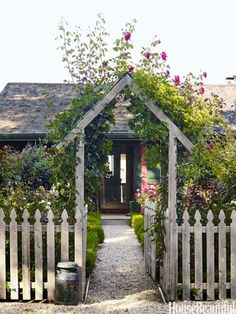 Rose covered archway frames front door of designer Podge Bune Hamptons beach cottage.