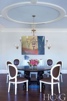 An antique chandelier from Hiden Galleries in Stamford, Connecticut, amplifies the dining room, which features a Côté France table surrounded by Oly Studio chairs. A Jeff Muhs oil painting hangs above a white-lacquer bombé chest.