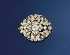 A Victorian diamond brooch  Designed as a brilliant-cut diamond oval openwork foliate cluster with central solitaire diamond and diamond two stone shoulders, circa 1890, in gold and silver mount