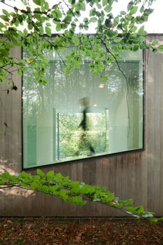 In the area of Bruges in Belgium, the local architects Benny Govaert & Damiaan Vanhoutte designed Villa Roces, a family house and a conceptual home. The oblong terrain and the wooded surroundings led the architects to the designing solution of a wide glass box with a high degree of transparency in order to provide a response to the minimum light. A big wall along the house was also built for the same reason: the intention to reflect the light and the presence of the forest.