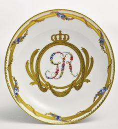A rare Russian Imperial presentation cup and saucer, Imperial Porcelain Manufactory, St. Petersburg, Period of Catherine II (1762-1796) cylindrical tapering form, both cup and saucer with the floriate initials GR within two-color, ciselé gilt wreath surmounted by a princely crown and from which is suspended a ribbon-tied swag, the rim of the cup and the border of the saucer similarly decorated with varicolor gilt band intertwined with festoons of blue roses with gilt leaves, the handle…