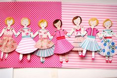 Hand painted with watercolour, with skirts made from cupcake cases, joined together with tiny paper fasteners.