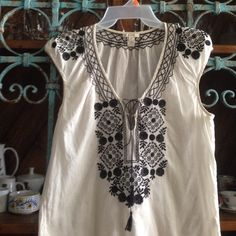 """BOHO EMBROIDERED BLOUSE by J. CREW Details: Cream colored blouse with Black embroidery on front and back of collar (with stretch), ties in front with hanging tassels and slits on the sides.  Material:  lightweight cotton  Size XS Measurements: 24"""" from shoulder to bottom of hem, 19.5"""" from pit to pit In excellent condition J. Crew Tops Blouses"""