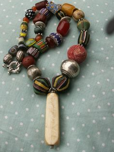 by Anne Marie | An old pre-ban ivory pendant from the Congo is attached to a necklace of a small collection of antique Venetian beads from the late 1800s/early 1900s. There are King Beads, Fancy Beads, Hudson Bay beads, chevron beads, Millefiori, feather beads, Skunk beads, sterling silver, etc. | BeadArt Austria Designs