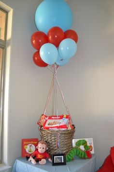 """Story Book baby shower theme: A """"hot air balloon"""" for the diapers that guests brought along with books, """"The Very Hungry Caterpillar"""" and """"Curious George"""" and their coordinating plush toys near a picture of the ultrasound in a frame."""