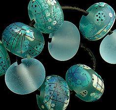 set of 10 glass beads in aqua and teals. Accents include fine stringer work.