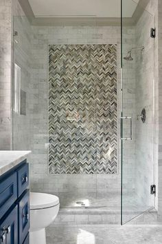 Blue and gray chevron accent tiles are fitted in a seamless glass shower finished with gray marble subway surround tiles and a polished nickel shower head fixed facing a niche. Shower Stall, Blue Bathroom, Shower Surround, Mosaic Bathroom Tile, Bathroom Shower Tile, Chevron Bathroom, Tile Bathroom, Mosaic Tile Bathroom Wall, Shower Wall