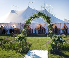 The entrance to a grand, open-air reception tent is just steps away from a beautiful ceremony space.
