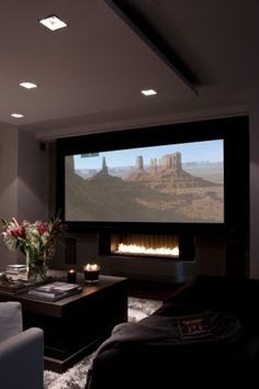 A dramatically dark home theater with an espresso coffee table and both espresso and gray upholstered sofas
