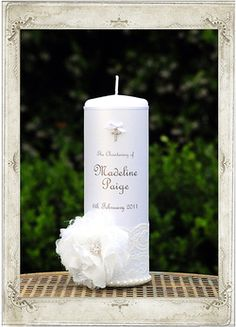 Angelic Dream Christening Candle. This divine Christening candle is adorned in a delicate antique white lace and is trimmed with pearls. It features a stunning white lacy flower which is accented with a round clustered diamante embellishment and is finished with a white satin ribbon and a petite bow holding a dainty diamante cross. Your personalised details will be displayed in a French style script, set on a white pearl background. Perfect for any occasion. Free gift with every order.