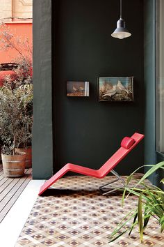 a red Maarten van Severen chaise lounge in this rustic and stylish outdoor space with a unique patterned tile floor