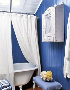 I love the textures here...the blue wall...and the claw foot tub!