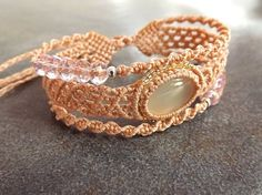 A charming, lacy macrame bracelet in three tiers. The center tier features a dainty pale green chalcedony cabochon framed with tiny silver lined seed beads. The outer tiers feature sparkling rose faceted crystal rondelle beads and small silver plated metal seed beads. The bracelet closes