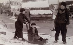 12-11-11  Child is pushed in rustic baby carriage on sled runners in the snow. 1915