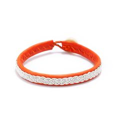 The layered look is hotter than ever especially on trendy wrists. Add this orange leather bracelet with pewter thread, Swarovski crystals and a bone button to your accessory treasure trove. Find it on Splendor Designs