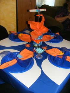tables covered in royal blue clothes with posterboard clouds as placemats, blue plates, orange napkins tied with a bit of glitz ribbon topped off with a small airplane whistle.  The centerpieces had orange tissue, blue polka dot ribbon with foam airplanes on top