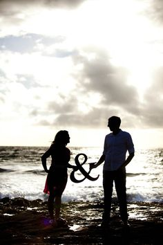 Engagement photo at the beach with an ampersand - Photo credit: Nick Corona