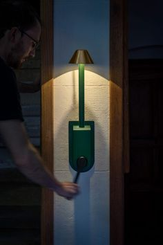 The lamp consists of brass shade and a deep green, milled aluminium body, which can be docked with the matching wall-mounted or tabletop charging stations that are strewn around the castle.  Cranking up the generator charges the small battery that is integrated into the stem. One minute of cranking is able to power its LEDs for more than six minutes. Wall Appliques, Textile Company, Royal College Of Art, Energy Consumption, Off The Grid, Building Design, Candle Sconces, Lighting Design, Floor Lamp