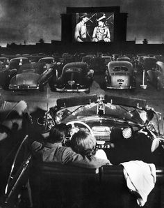vintagegal: Young couple snuggling behind the wheel of his convertible as they watch large screen action behind rows of cars at a drive-in movie theater. Los Angeles, 1949 Lamenting the fact that Sydney has a grand total of one drive-in cinema and it shows uniformly awful movies.