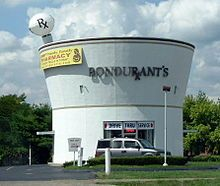 Bondurant's Pharmacy drug store opened in 1974, built in the shape of a giant mortar & pestle, a common tool of the pharmacist. It is located on Village Drive near Versailles Road in Lexington, Kentucky. The pestle projects 19 feet above the building which is 30 feet high. It has a diameter of about 32 feet. There are 2 drive-thru windows, along with parking spaces for customers who want to walk into the store. The 2nd floor was initially designed as an apartment for the pharmacist.