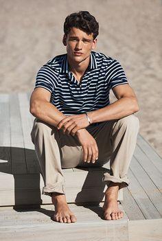 Barefoot man on beach wearing khaki pants & striped Polo shirt