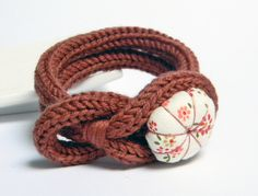 Cinnamon knitted wool yarn bracelet, handmade fabric flower button, tied up, yarn jewelry. €18.00, via Etsy.