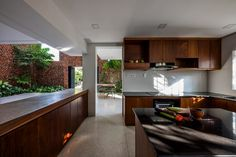 The practice has otherwise kept the material palette of the home very simple – exposed-aggregate concrete covers the floor and dark wood has been used to craft the cabinetry in the kitchen.