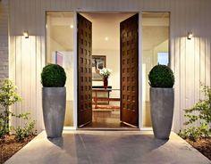 porta madeira escura trabalhada duas folhas vasos hall entrada