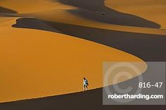Tourist walking along a giant sand dune, Merzouga, Morocco, North Africa, Africa