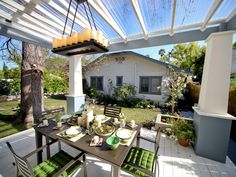 Adding a clear plastic cover to a pergola protects an outdoor entertaining space from the elements without sacrificing sunlight.