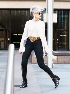 Accidental Icon wears a white top, statement belt, zip-up pants, sandals, drop earrings, and gray sunglasses