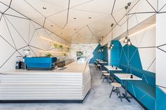 This compact contemporary cafe has a tessellated pattern that wraps from the walls around to the ceiling.