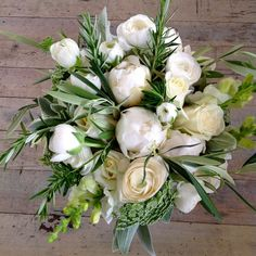 Handtied bouquet with a selection of beautiful blooms including Peonies, White Avalanche Roses, White Ranuculas, White Snap Dragons in white/cream colour tones, with accomanying Rosemary, Green foliage
