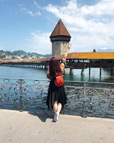 CHLOE.ROXANE - Instagram : Discovering Lucerne, Switzerland in an outfit with a flower crop top, a black skirt, white sneakers and a small red backpack. View of the Chapel Bridge in Lucerne.