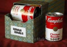 Canned good storage made from a empty canned drink box covered with fabric or paper. You can attach a small block of wood at the back to make the cans self-dispense!