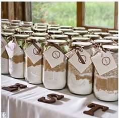 "A Rustic Wedding - The creative couple made their own favors: mason jars filled with ingredients for baking cookies -- guests could choose between chocolate chip and oatmeal raisin. They bought the jars online and filled them with the baking goods they bought at Sam's Club. Then, they decorated them with ribbon and recipe cards stamped with a ""thank-you."""