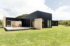 Designed by Tane Cox, this stunning piece of architecture in the hills surrounding Raglan, New Zealand was built with a focus on natural, sustainable resources. Click through to take a look at the inside, where industrial and concrete trends are warned with touches of natural wood and pops of colour.
