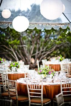 reception table setting - dark gold table cloths, purple and green centerpieces, white vintage style chairs, and hanging white chinese paper globe lanterns - photo by New Mexico based wedding photographers Twin Lens