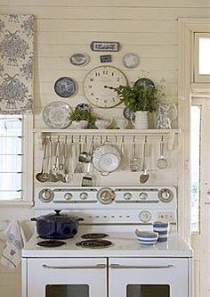 cute shelf above stove with hanging utensils