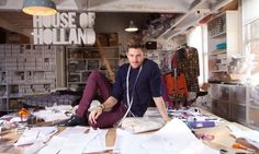 Henry Holland, tape measure round his neck, sits on his busy desk in his east London studio